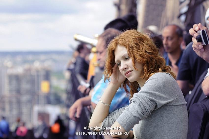 Sad girl among tourists on Eiffel Tower